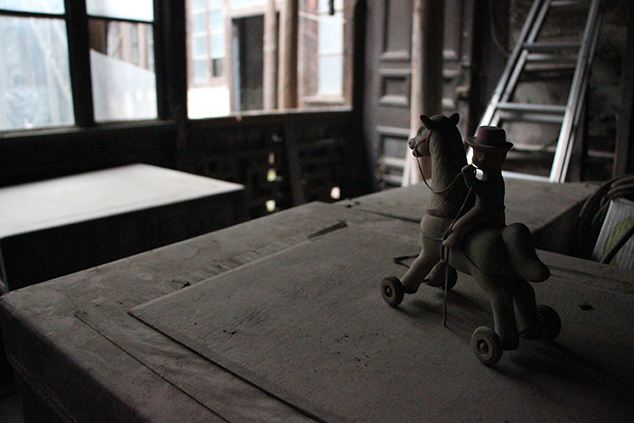 An old toy looks out over the tumble-down buildings