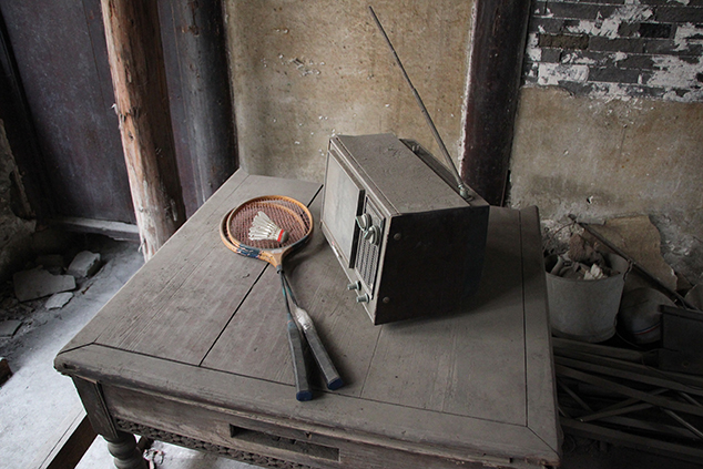 An old TV set and badminton rackets sit on one table